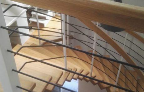 Dębowe schody gięte samonośne na drewnianej belce centralnej